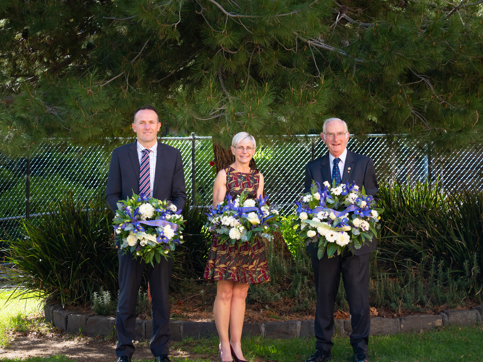 Mark Dewar, Susan Ogden and Alan Collier stand under the lone pine tree at Dandenong High School with their ANZAC wreaths.